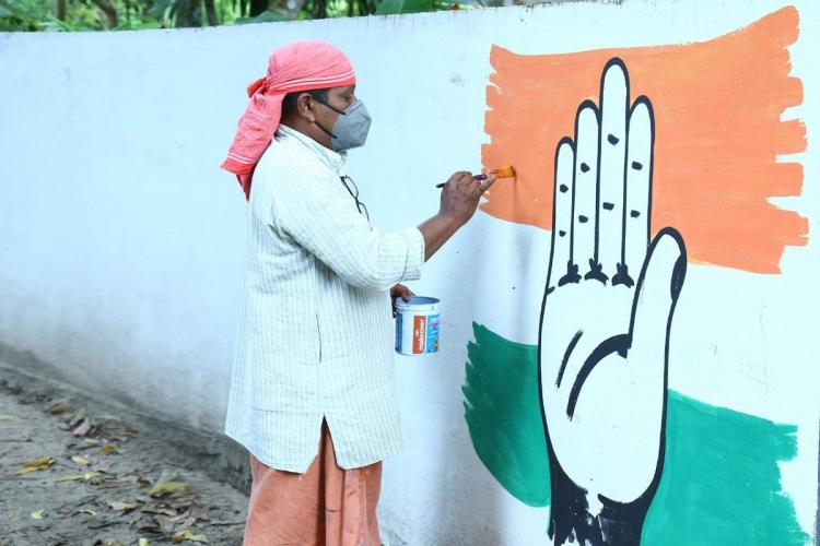Rajesh draws the hand symbol of the UDF on a wall in his work clothes