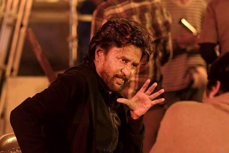 Rajinikanth in black and holding his hand up in Petta still
