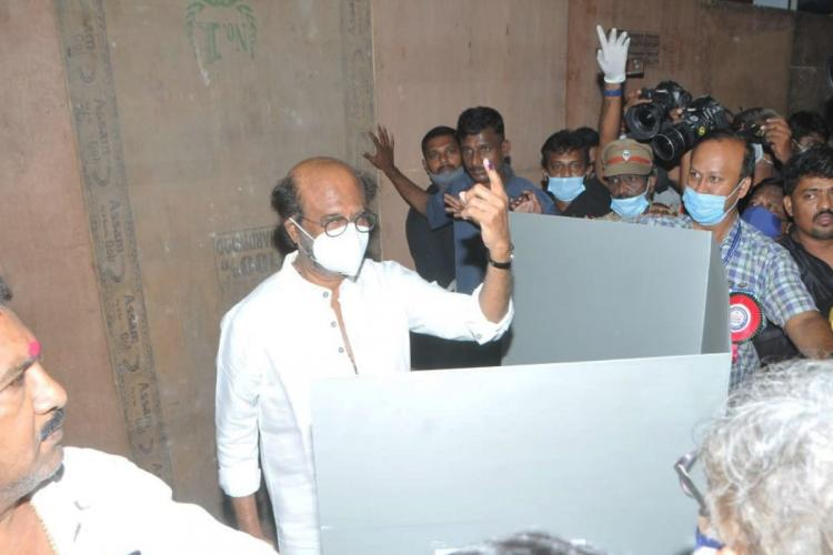 Rajinikanth shows his inked left finger to the media after voting on April 6 in Chennai