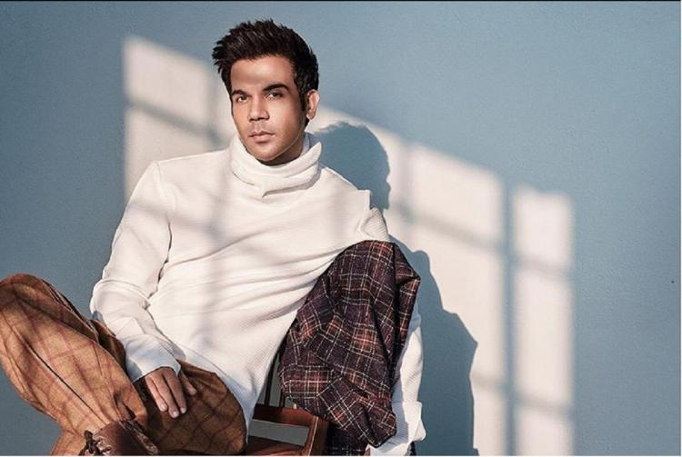 Rajkummar Rao in a white shirt and brown pants sitting against a wall with sunlight from a window on him
