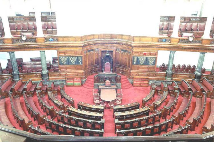 Rajya Sabha chamber with red carpets and red seats arranged in semi-circle rows