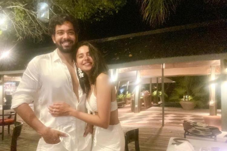 Rakul Preet with her brother Aman Preet on a holiday in Maldives both are wearing white clothes and smiling
