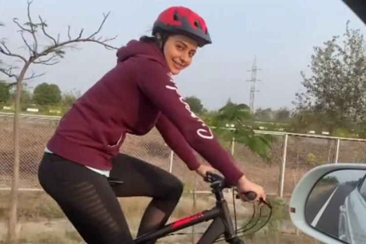 Rakul Preet Singh on a cycle smiling at the person shooting her video from inside a car