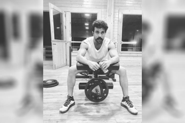 Ram Charan is seen seated on a leg machine in a gym.