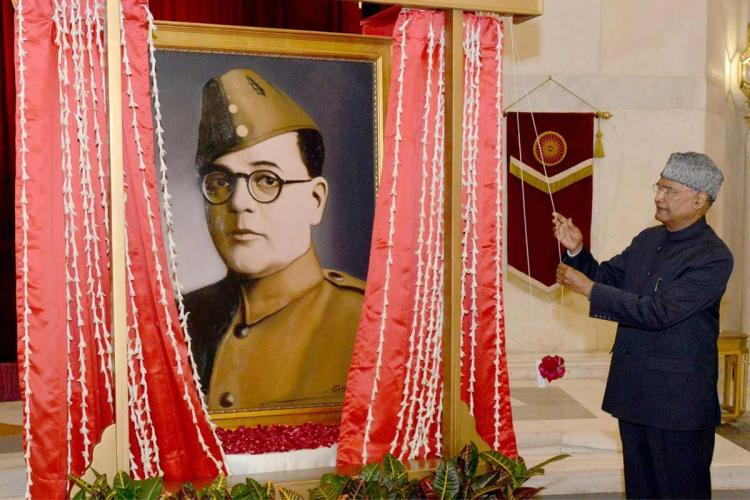 President Ram Nath Kovind standing in front of of a Subash Chandra Bose portrait as he unveils it
