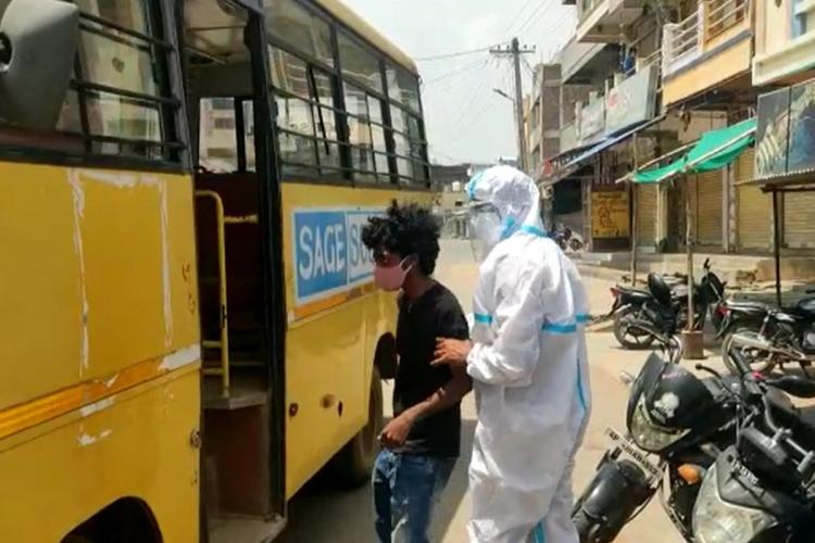 A police man wearing a PPE kit escorting a youngster into a bus