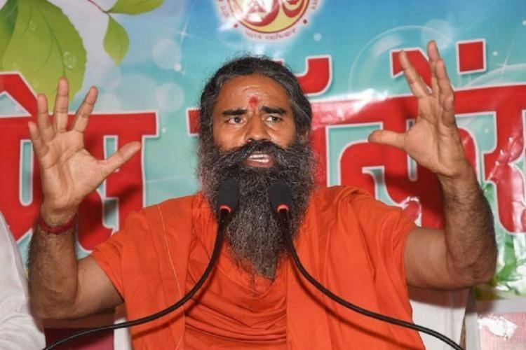 Baba Ramdev in orange garments in front of a mic