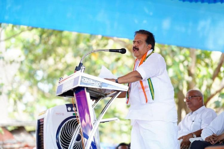 Chennithala in white khaddar stands sideways before a microphone in a podium under a blue sheet