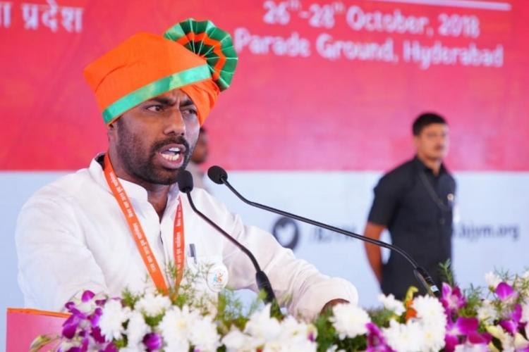 BJP Andhra Pradesh State Secretary Rameshnaidu Nagothu speaking into a mic on stage wearing a saffrom turban