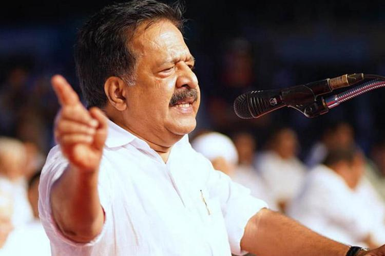 Ramesh Chennithala speaks before a microphone his hand in the air