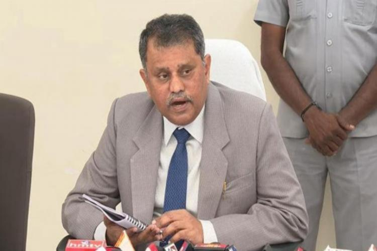 Ramesh Kumar in a grey suit and blue tie and white shirt addressing media speaking into mics with his face turned towards his left