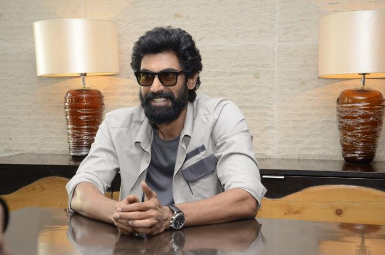 Rana Daggubati posing for a picture by wearing a gray coloured shirt and googles