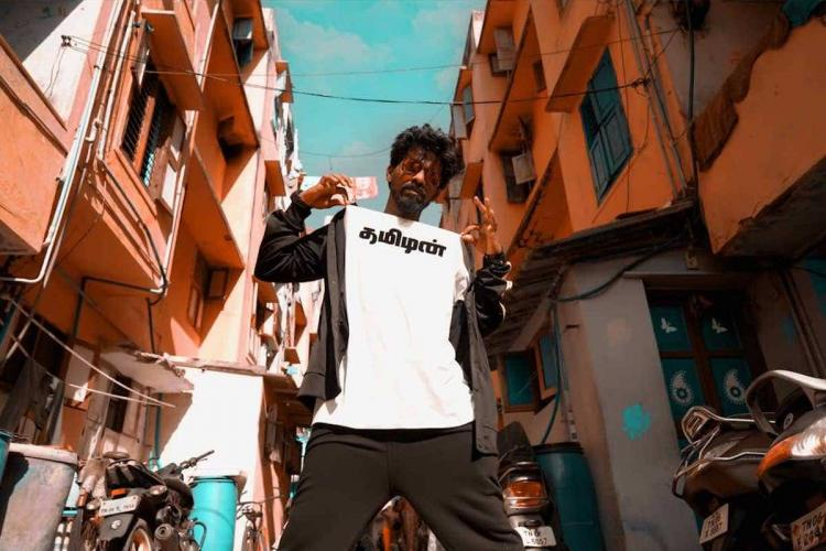 Rapper Nigavithran in a white t-shirt with the words Tamizhan written in black in Tamil black pants and black jacket