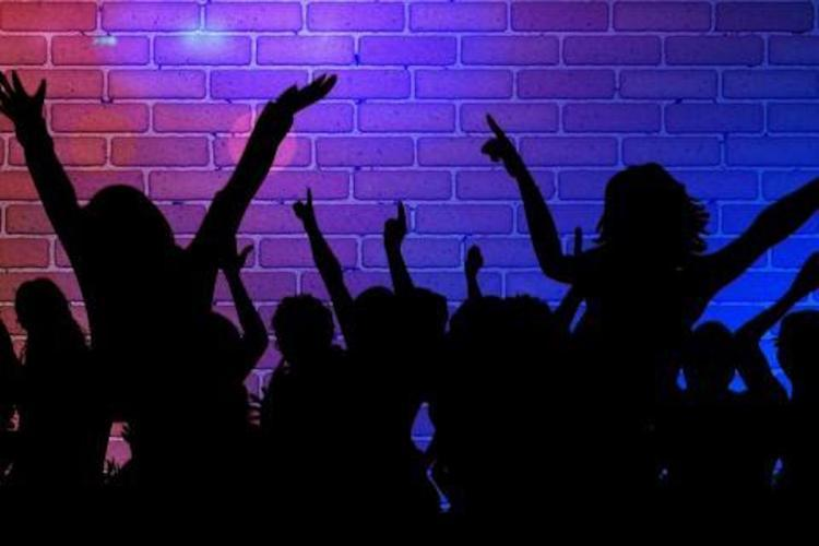 A silhouette picture of people at a Rave Party