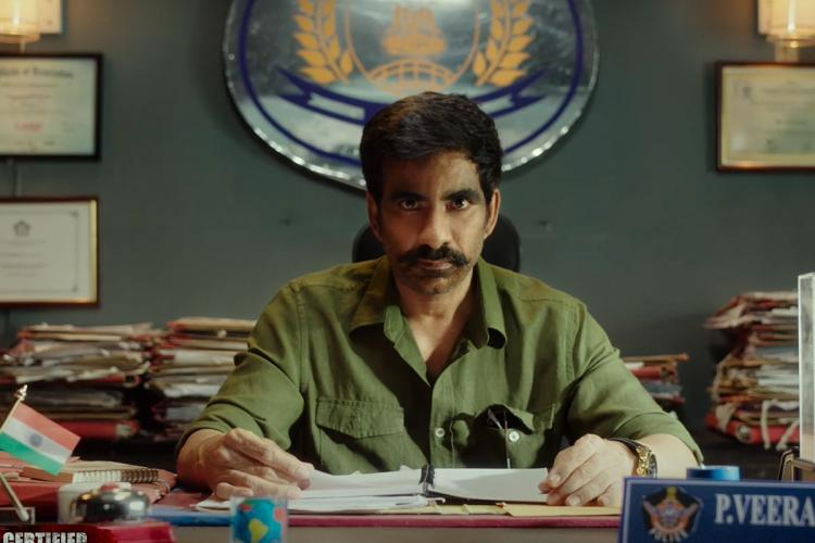 Ravi Teja in a green shirt in a fierce look checking files in an office set up