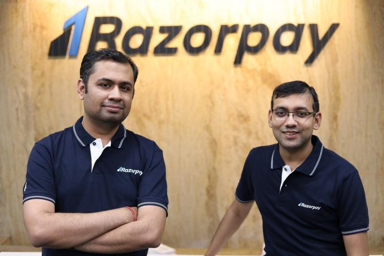 Razorpays founders Harshil Mathur and Shashank Kumar in company t-shirts standing against company logo
