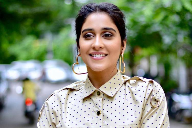 Actor Regina Cassandra wearing a beige polka dotted collared outfit and large golden coloured heart-shaped earrings She is smiling and looking slightly to her right