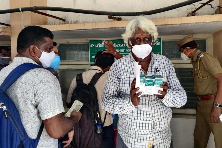 An old man with white hair poses for the camera after procuring some vials of Remdesivir in Chennai