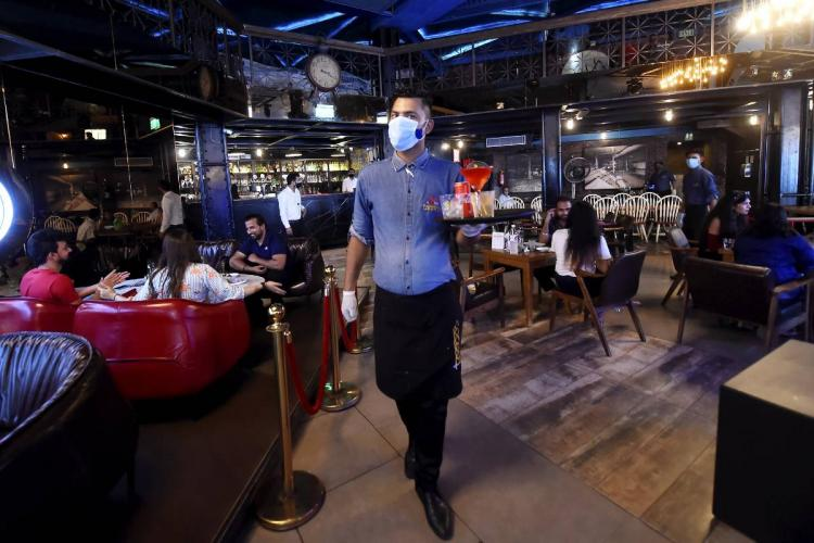 A staff member wearing mask working at a bar and restaurant after Delhi government permitted reopening of bars with 50% seating occupancy