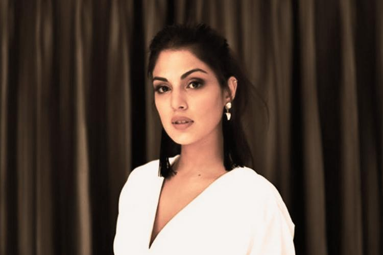 Bollywood actor Rhea Chakraborty dressed in white with her hair tied behind looking into the camera
