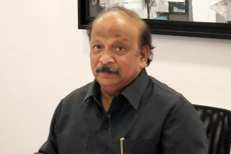 Roshan Baig seated wearing a black shirt looking unsmiling at the camera