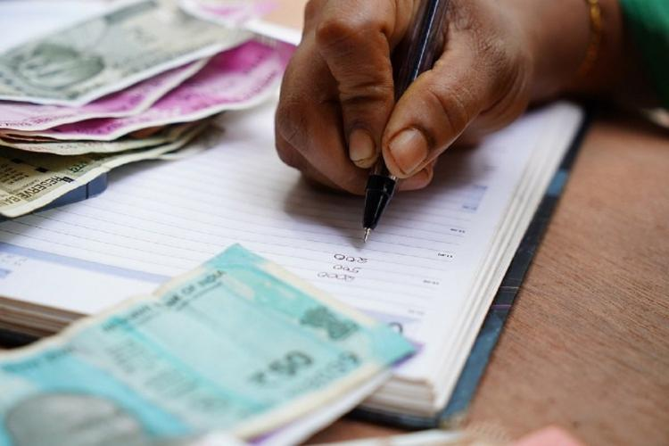 a person doing accounts with money around the notebook