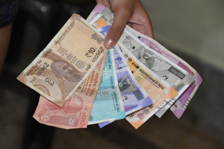 A person holding notes of different denominations