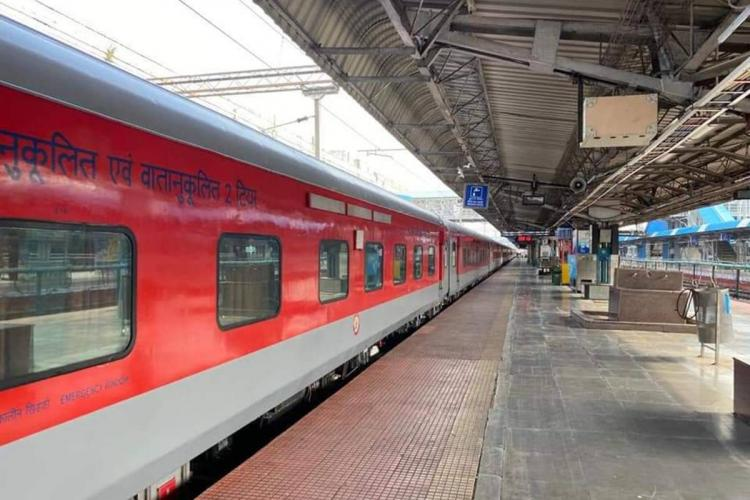 South Central Railway train undergoing speed test the air conditioned coach is of red colour and has stopped next to a platform