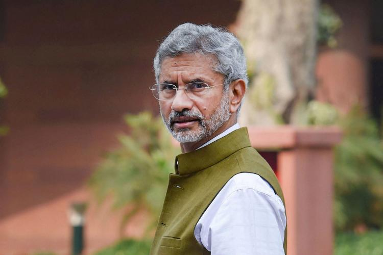 India's External Affairs Minister Dr S Jaishankar in a green vest and white shirt, looking into the camera.