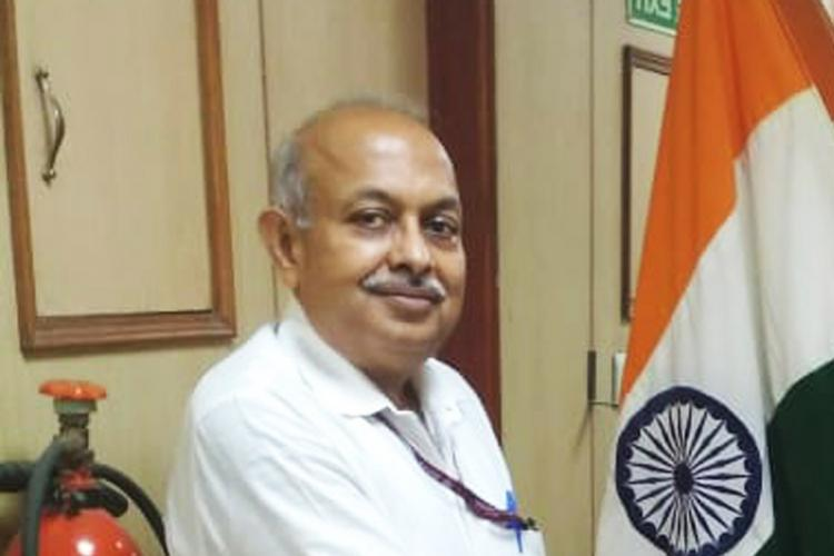 ED director Sanjay Kumar Mishra is seen smiling in the image The Indian flag is seen in the background