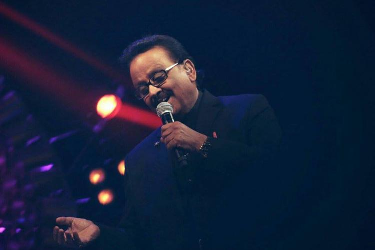 SP Balasubrahmanyam singing at an event wearing a dark coat light only on his face mic held in left hand