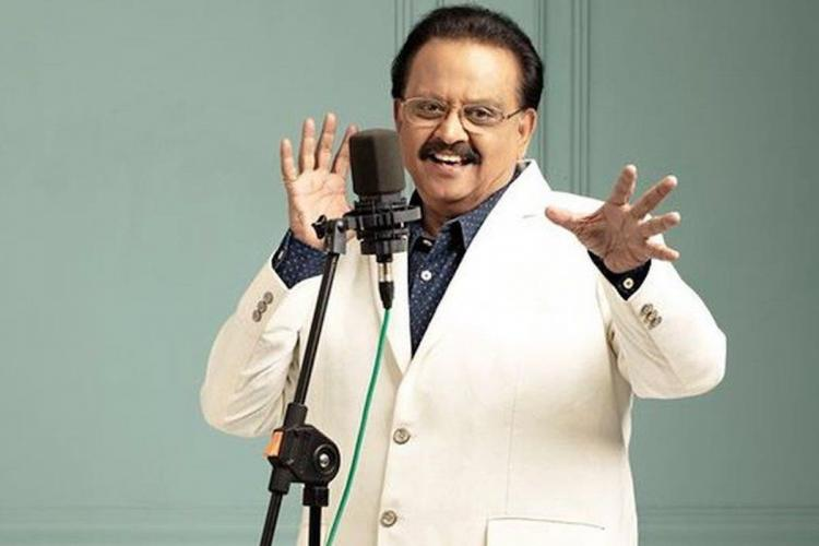 SPB in front of a mic posing like hes singing