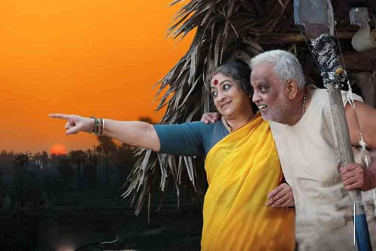 Actors Lakshmi and SPB in a still from the Telugu film Mithunam Both are standing in front of a hut Lakshmi is wearing a yellow sari pointing to something far with her right hand while SPB watches in a white vest