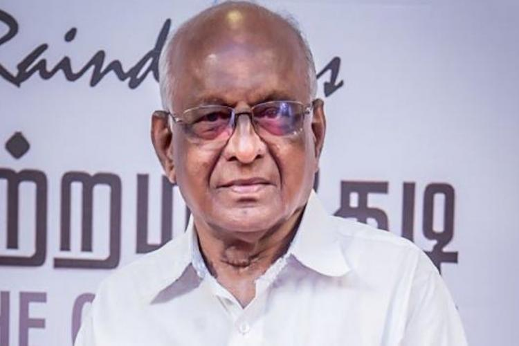 SP Muthuraman wearing glasses and a white shirt