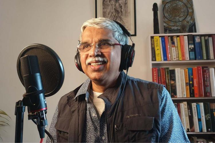 A man with grey hair and moustache smiles standing in front of a microphone and wearing headphones, recording, as in the background you see a book shelf and painting
