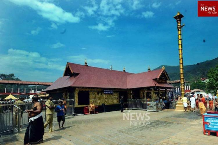 Sabarimala temple set against clear blue sky without the crowd sparing a couple of people