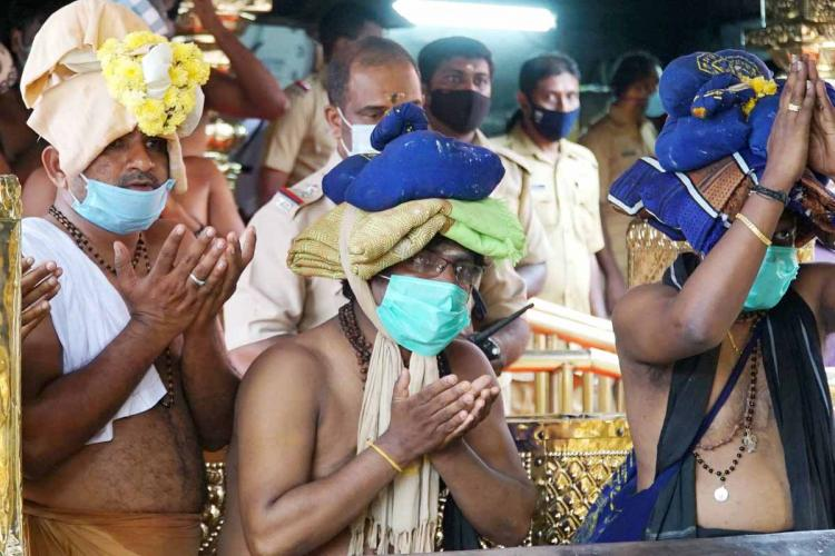 Devotees wearing masks in Sabarimala temple. Three men are folding hands and praying