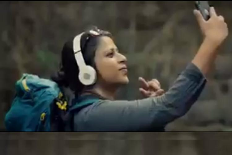 Side profile of a young woman with a backpack white headphones taking a selfie holding the V symbol