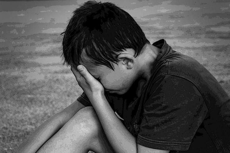 Black and white picture of a boy sitting with his knees up and covering his face with his hand