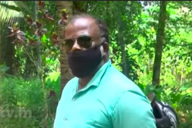 A man in a teal T shirt with sunglasses and a black mask
