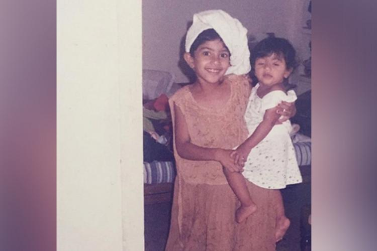 Sai Pallavi as a child carrying her baby sister Pooja while wearing a towel on her head