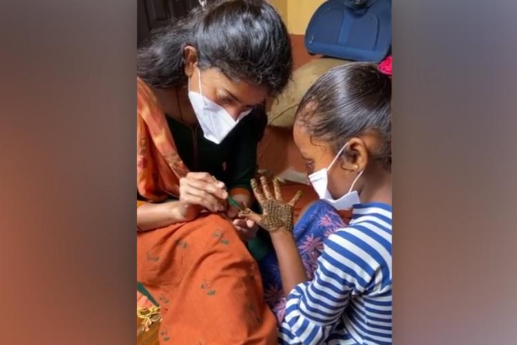 Sai Pallaci in mask and orange kurta putting mehendi for girl in blue dress