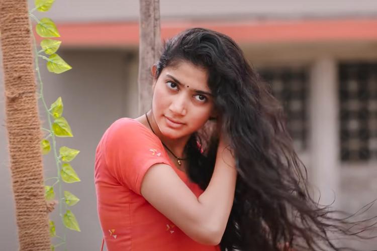 Sai Pallavi in an orange kurta drying her hair
