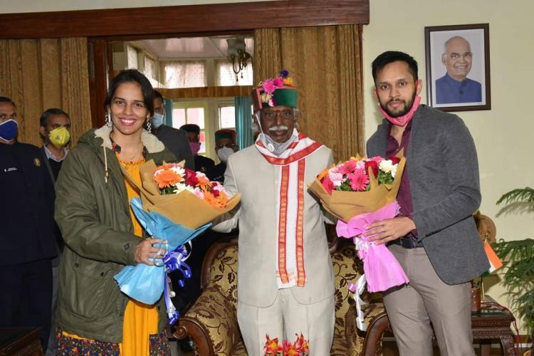 Saina and Kashyap with bouquets for Governor Bandaru Dattatreya