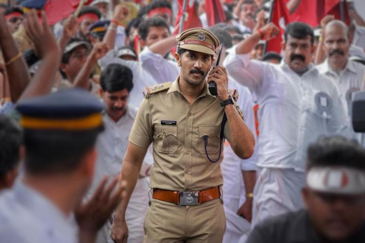 Dulquer is seen as a cop and is seen speaking over walkie-talkie while a crowd of protesters are seen in the background