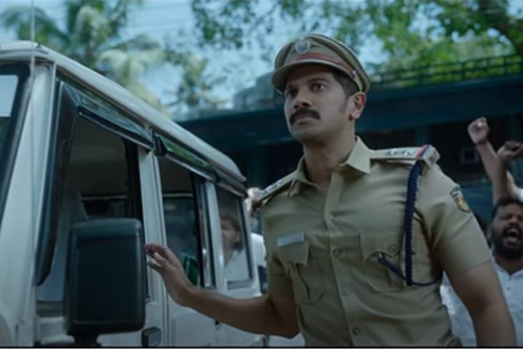 Dulquer in police uniform has gotten out of a white police vehicle and is closing the door facing ahead of him