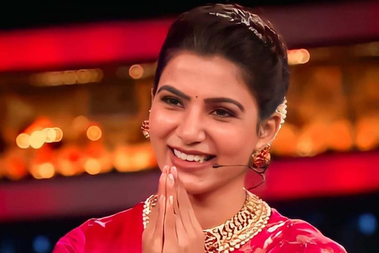 Samantha wears a dark pink Sari smiles and has her palms held together in the form of a namasta