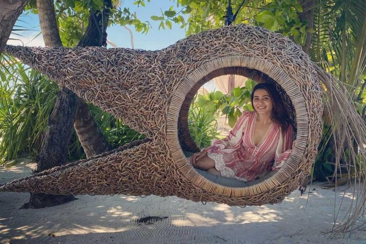 Samantha seated in a heron shaped chair at a beach resort in the Maldives