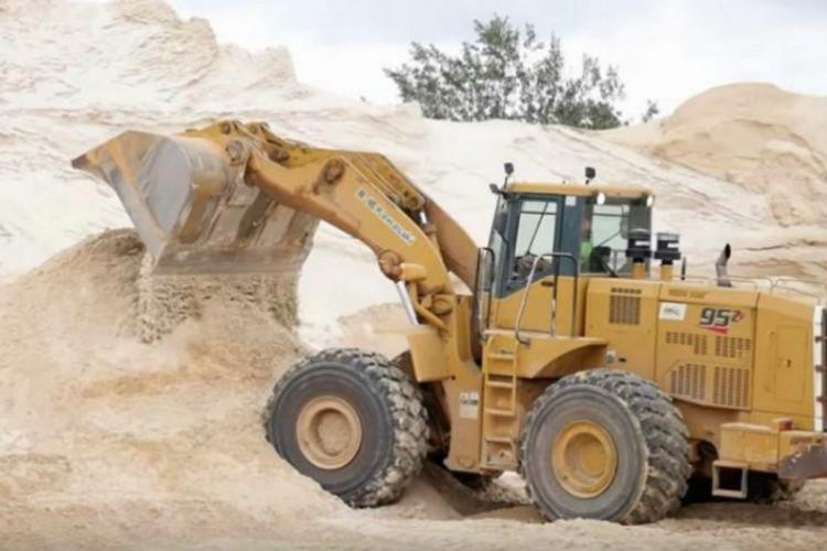 An excavator taking out sand from sand reach