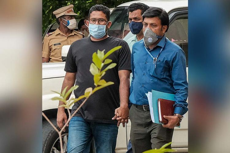Kerala gold smuggling accused Sandeep Nair is being presented in court wearing a black t shirt and jeans In the background investigation officials are seen escorting him